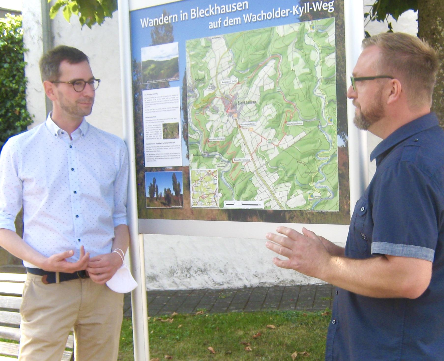 Jens Jenssen und Markus Göbel vor der Info-Tafel zum Wacholder-Wanderweg, der rund um Bleckhausen führt.